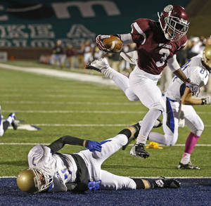 Photo - Edmond Memorial's Waylan Anderson leaps over Choctaw's Kennedy Humphrey before the play was called back due to a penalty on Edmond Memorial during their high school football game at Wantland Stadium in Edmond, Thursday, October 17, 2013. Photo by Bryan Terry, The Oklahoman