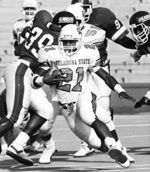 Photo - Oklahoma State University running back Barry Sanders breaks through the line for first down yardage during first quarter action in the OSU-Kansas college football game in Stillwater on November 12, 1988.  The Cowboys beat the Jayhawks by a 63-24 score that day. Staff photo by Jim Argo.