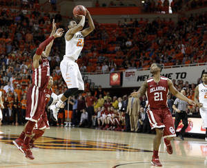 Photo - Oklahoma State's Markel Brown (22) attempts a final tying shot during the men's Bedlam college game between Oklahoma and Oklahoma State at Gallagher-Iba Arena in Stillwater, Okla., Saturday, Feb. 15, 2014. Photo by Sarah Phipps, The Oklahoman
