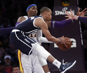 photo - Oklahoma City Thunder guard Russell Westbrook,front, passes as Los Angeles Lakers center Dwight Howard (12) defends in the first half of an NBA basketball game in Los Angeles Sunday, Jan. 27, 2013. (AP Photo/Reed Saxon)  ORG XMIT: LAS102