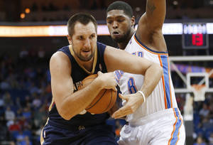 Photo - New Orleans Pelicans forward Ryan Anderson, left, drives past Oklahoma City Thunder forward Ryan Gomes during the first quarter of an NBA basketball preseason game in Tulsa, Okla., Thursday, Oct. 17, 2013. (AP Photo/Sue Ogrocki) ORG XMIT: OKSO113