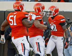 photo - CELEBRATION: Oklahoma State's Isaiah Anderson (82) celebrates after a touchdown with Oklahoma State's Brandon Webb (51) and Lane Taylor (68) during a college football game between Oklahoma State University (OSU) and Texas Tech University (TTU) at Boone Pickens Stadium in Stillwater, Okla., Saturday, Nov. 17, 2012.  Photo by Bryan Terry, The Oklahoman