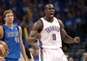 photo - Oklahoma City's Serge Ibaka (9) celebrates after a offensive foul on Dallas' Dirk Nowitzki (41) during game one of the first round in the NBA playoffs between the Oklahoma City Thunder and the Dallas Mavericks at Chesapeake Energy Arena in Oklahoma City, Saturday, April 28, 2012. Photo by Sarah Phipps, The Oklahoman