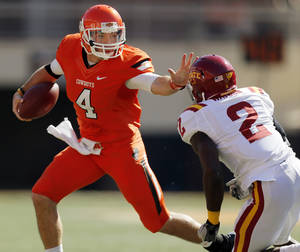 photo - Oklahoma State's J.W. Walsh (4) tries to get past Iowa State's Jansen Watson (2) on a keeper during a college football game between Oklahoma State University (OSU) and Iowa State University (ISU) at Boone Pickens Stadium in Stillwater, Okla., Saturday, Oct. 20, 2012. Photo by Nate Billings, The Oklahoman