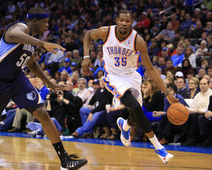 Photo - Memphis Grizzlies forward Zach Randolph (50) defends as Oklahoma City Thunder forward Kevin Durant (35) drives to the basket during the third quarter of an NBA basketball game on Monday, Feb. 3, 2014, in Oklahoma City. Oklahoma City won 86-77. (AP Photo/Alonzo Adams)
