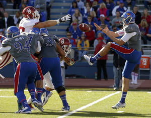 Photo - OU's Matt Dimon (90) and OU's Londell Taylor (31) leap forward as OU blocks the punt of KU's Trevor Pardula (16)during the college football game between the University of Oklahoma Sooners (OU) and the University of Kansas Jayhawks (KU) at Memorial Stadium in Lawrence, Kan., Saturday, Oct. 19, 2013. Photo by Bryan Terry, The Oklahoman