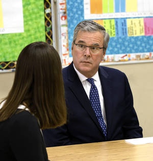 Photo -  Former Florida Gov. Jeb Bush accompanied Oklahoma Gov. Mary Fallin on a tour April 8, 2014, at KIPP Reach College Preparatory in northeast Oklahoma City  to discuss successful teaching and learning strategies with students and teachers. Bush listens to ideas from seventh grade reading teacher Betsy Blanks. KIPP, part of a highly successful chain of national charter schools, received an A grade on the recent state report cards and is an example of a successful urban school that has overcome high poverty rates. Bush championed a number of major education reforms and initiative while governor of Florida.  Photo by Jim Beckel, The Oklahoman  <strong>Jim Beckel -   </strong>