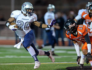 Photo - Freedom High's Joe Mixon (20) left, tries to get past the Pittsburg High defense in the second quarter of their North Coast Section playoff football game in Pittsburg, Calif., on Friday, Nov. 22, 2013. (Doug Duran/Bay Area News Group)