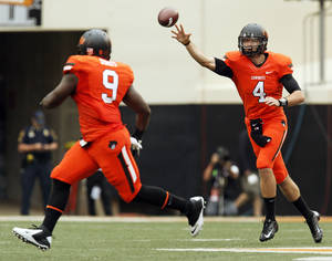Photo - OSU quarterback J.W. Walsh (4) passes the ball to Kye Staley (9) in the first quarter during a college football game between Oklahoma State University (OSU) and the University of Louisiana-Lafayette (ULL) at Boone Pickens Stadium in Stillwater, Okla., Saturday, Sept. 15, 2012. Staley took the ball 52 yards for a touchdown. Photo by Nate Billings, The Oklahoman