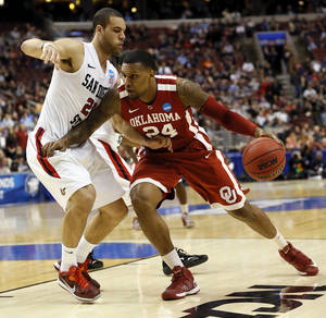 Photo - Oklahoma's Romero Osby (24) works against San Diego State's JJ O'Brien (20) during a game between the University of Oklahoma and San Diego State in the second round of the NCAA men's college basketball tournament at the Wells Fargo Center in Philadelphia, Friday, March 22, 2013. Photo by Nate Billings, The Oklahoman