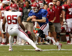 Photo - Trevor Knight, left, runs with the ball as Geneo Grissom defends during OU's spring game on Saturday. Knight had a so-so passing day, but was missing some of his experienced pass catchers.                    Photo by Steve Sisney, The Oklahoman