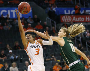 Photo - Oklahoma State guard Tiffany Bias (3) shoots as South Florida guard Ariadna Pujol (11) defends in the first half of an NCAA college basketball game at the All College Classic in Oklahoma City, Saturday, Dec. 14, 2013. (AP Photo/Sue Ogrocki)