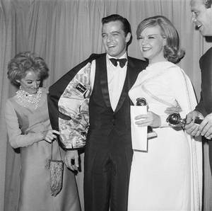 photo - Phyllis Diller checks out  Robert Goulet's coat  as they pose for photographers at  the Hollywood Foreign Press Association and Golden Globe Awards  in Hollywood, Calif.,  January 31, 1966.     At right is Ann Francis. (AP Photo/ Harold Matosian)