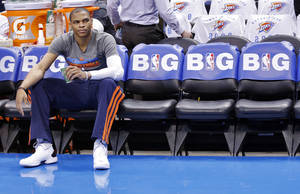 Photo - NBA BASKETBALL: Russell Westbrook sits on the bench before the start of Game 2 in the first round of the NBA playoffs between the Oklahoma City Thunder and the Houston Rockets at Chesapeake Energy Arena in Oklahoma City, Wednesday, April 24, 2013. Photo by Chris Landsberger, The Oklahoman