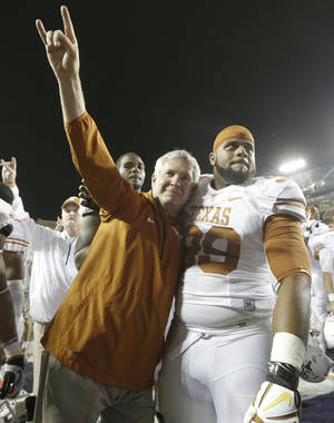 Photo - Texas head coach Mack Brown, left, hugs Texas defensive tackle Desmond Jackson (99) as he does the hook 'em horns sign  after their NCAA college football game against  TCU early Sunday morning, Oct. 27, 2013, in Fort Worth, Texas.  Texas won 30-7. (AP Photo/LM Otero)