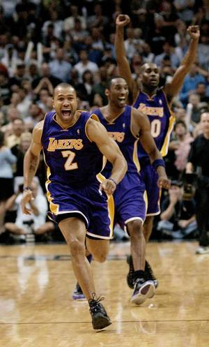 Photo - ABOVE: Derek Fisher, front, celebrates with Los Angeles Lakers teammates Kobe Bryant, center, and Gary Payton after his buzzer-beater defeated San Antonio in Game 5 of the 2004 Western Conference Semifinals. BELOW: Actor Edward Norton wore a T-shirt supporting Fisher before Game 6. AP ARCHIVE PHOTOS