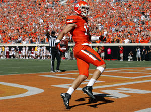 photo - Oklahoma State's Charlie Moore (17) celebrates a touchdown in the second quarter during a college football game between Oklahoma State University (OSU) and Iowa State University (ISU) at Boone Pickens Stadium in Stillwater, Okla., Saturday, Oct. 20, 2012. Photo by Sarah Phipps, The Oklahoman