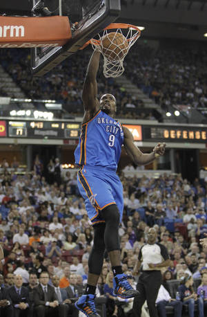 Photo - Oklahoma City Thunder center Serge Ibaka, of the Congo, stuffs during the first quarter against the Sacramento Kings in an NBA basketball game, Tuesday, April 8, 2014, in Sacramento, Calif. (AP Photo/Rich Pedroncelli)