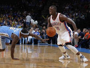 photo - EXHIBITION NBA BASKETBALL GAME: Oklahoma City's Reggie Jackson (15) drives the ball past Denver's Ty Lawson (3) during the NBA preseason basketball game between the Oklahoma City Thunder and the Denver Nuggets at the Chesapeake Energy Arena, Sunday, Oct. 21, 2012. Photo by Garett Fisbeck, The Oklahoman
