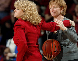 photo - Head coach Sherri Coale hands the ball to assistant coach Jan Ross after being given the the game ball after her 300th win.  The University of Oklahoma (OU) Sooners women&#039;s college basketball team defeated the Kansas University (KU) Jayhawks 81-69 at the Lloyd Noble Center on Saturday, Jan. 23, 2010, in Norman, Okla.  Photo by Steve Sisney, The Oklahoman 