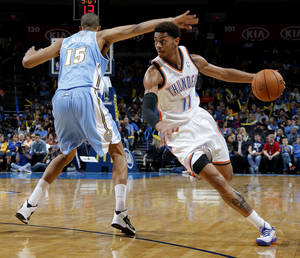 Photo - Oklahoma City 's Jeremy Lamb (11) goes past Denver's  Anthony Randolph (15) during an NBA preseason game between the Oklahoma City Thunder and the Denver Nuggets at Chesapeake Energy Arena on Tuesday, october 15, 2013. Tuesday, Oct. 15, 2013. Photo by Bryan Terry, The Oklahoman