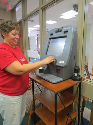 Photo - Orvis Risner Elementary School Registrar Amy  Arbuckle demonstrates how to use the school's  visitor monitoring system called LobbyGuard. All schools in the Edmond district have been outfitted with the kiosks. PHOTO PROVIDED