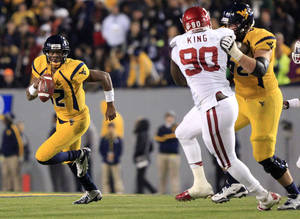 photo - West Virginia quarterback Geno Smith (12) carries the ball as Curtis Feigt (62) blocks Oklahoma&#039;s David King (90) during the fourth quarter of their NCAA college football game against Oklahoma in Morgantown, W.Va., on Saturday, Nov. 17, 2012. Oklahoma won 50-49. (AP Photo/Christopher Jackson)
