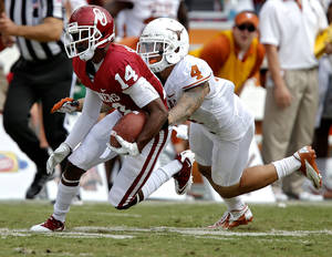 Photo - OU's Jalen Saunders (14) is brought down by UT's Kenny Vaccaro (4) during the Red River Rivalry college football game between the University of Oklahoma (OU) and the University of Texas (UT) at the Cotton Bowl in Dallas, Saturday, Oct. 13, 2012. Photo by Chris Landsberger, The Oklahoman