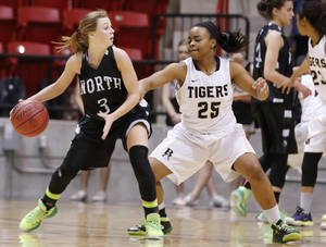 Photo - Broken Arrow's Tierra Jones, right, guards Norman North's Paige Canty during the class 6A girls state basketball tournament at Skiatook.