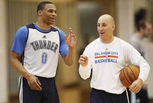 Photo - Thunder guard Russell Westbrook speaks with a coach before speaking to the media after practice at the Thunder Practice Facility in Oklahoma City on Monday, April 26, 2014. Photo by KT King/The Oklahoman