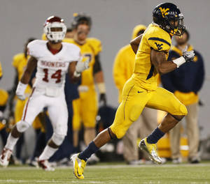 photo - OU: West Virginia's Tavon Austin (1) carries the ball for a long gain in the fourth quarter during a college football game between the University of Oklahoma and West Virginia University on Mountaineer Field at Milan Puskar Stadium in Morgantown, W. Va., Nov. 17, 2012. OU won, 50-49. Photo by Nate Billings, The Oklahoman