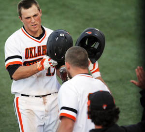 Photo - Oklahoma State base runner Gage Green (17) is congratulated as he returns to the bench after hitting a home run during a NCAA college baseball game between Oklahoma State University (OSU) and Arizona State University at Allie P. Reynolds stadium in Stillwater, Okla., Friday, May 2, 2014. Photo by KT King, The Oklahoman