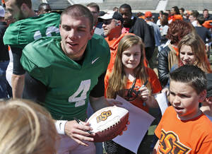 Photo - Oklahoma State quarterback J.W. Walsh (4) signs autographs for fans following an Orange Blitz NCAA college spring football practice in Stillwater, Okla., Saturday, April 5, 2014. (AP Photo/Sue Ogrocki)