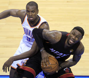 Photo - Miami Heat small forward LeBron James  is defended by Oklahoma City Thunder power forward Serge Ibaka (9) from Republic of Congo during the first half at Game 2 of the NBA finals basketball series, Thursday, June 14, 2012, in Oklahoma City. (AP Photo/Sue Ogrocki)  ORG XMIT: NBA139