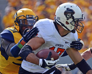 Photo - Oklahoma State receiver Charlie Moore (17) is tackled by West Virginia defender Isaiah Bruce (31) after a failed flea flicker in the third quarter of an NCAA college football game in Morgantown, W.Va., on Saturday, Sept. 28, 2013. (AP Photo/Tyler Evert)