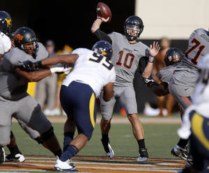 photo - Oklahoma State's Clint Chelf (10) throws the ball during a college football game between Oklahoma State University (OSU) and West Virginia University at Boone Pickens Stadium in Stillwater, Okla., Saturday, Nov. 10, 2012. Photo by Bryan Terry, The Oklahoman