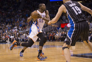 Photo - Oklahoma City Thunder's Kevin Durant (35) takes the ball to the hoop against Orlando Magic's Maurice Harkless (obscured) and Beno Udrih (19) during the second half of an NBA basketball game on Friday, March 22, 2013, in Orlando, Fla. The Thunder won 97-89. (AP Photo/Willie J. Allen Jr.) ORG XMIT: FLWA107