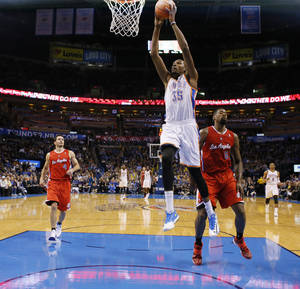 Photo - Oklahoma City's Kevin Durant (35) dunks between Los Angeles Clippers' J.J. Redick (4) and DeAndre Jordan (6) during an NBA basketball game between the Oklahoma City Thunder and the Los Angeles Clippers at Chesapeake Energy Arena in Oklahoma City, Thursday, Nov. 21, 2013. Oklahoma City won 105-91. Photo by Bryan Terry, The Oklahoman