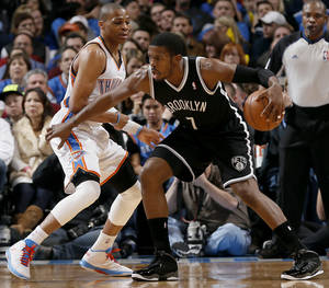 Photo - Oklahoma City's Russell Westbrook (0) defends on Brooklyn Nets' Joe Johnson (7) during the NBA basketball game between the Oklahoma City Thunder and the Brooklyn Nets at the Chesapeake Energy Arena on Wednesday, Jan. 2, 2013, in Oklahoma City, Okla. Photo by Chris Landsberger, The Oklahoman
