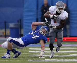 Photo - Oklahoma State's Joseph Randle (1) gets by Kansas 's Huldon Tharp (34) during the college football game between Oklahoma State University (OSU) and the University of Kansas (KU) at Memorial Stadium in Lawrence, Kan., Saturday, Oct. 13, 2012. Photo by Sarah Phipps, The Oklahoman