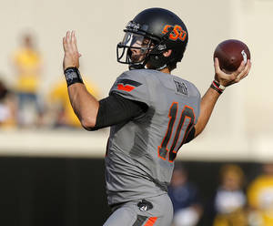 Photo - Oklahoma State's Clint Chelf (10) throws a touchdown pass during a college football game between Oklahoma State University (OSU) and the University of West Virginia at Boone Pickens Stadium in Stillwater, Okla., Saturday, Nov. 10, 2012. Photo by Bryan Terry, The Oklahoman