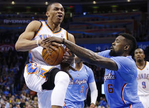 Photo - Los Angeles Clippers center DeAndre Jordan (6) attempts to take the ball away as Oklahoma City Thunder guard Russell Westbrook (0) drives in the fourth quarter of an NBA basketball game in Oklahoma City, Sunday, Feb. 23, 2014. Los Angeles won 125-117. (AP Photo/Sue Ogrocki)