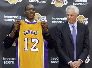 Photo - Center Dwight Howard, newly acquired by the Los Angeles Lakers from the Orlando Magic, poses with his Lakers jersey with Lakers general manager Mitch Kupchak, at a news conference Friday, Aug. 10, 2012, at the NBA basketball team's headquarters in El Segundo, Calif. (AP Photo/Reed Saxon) ORG XMIT: CARS204