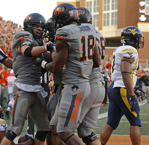 Photo - CELEBRATION: Oklahoma State's Charlie Moore (17) celebrates after a touchdown with Oklahoma State's Blake Jackson (18) as West Virginia's Doug Rigg (47) during a college football game between Oklahoma State University (OSU) and West Virginia University at Boone Pickens Stadium in Stillwater, Okla., Saturday, Nov. 10, 2012. Oklahoma State won 55-34. Photo by Bryan Terry, The Oklahoman