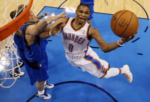 photo - Oklahoma City's Russell Westbrook (0) takes the ball to the hoop past Dallas' Delonte West (13) and Dirk Nowitzki (41)  during Game 2 of the first round in the NBA basketball  playoffs between the Oklahoma City Thunder and the Dallas Mavericks at Chesapeake Energy Arena in Oklahoma City, Monday, April 30, 2012. Photo by Nate Billings, The Oklahoman