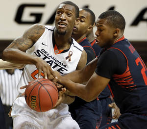 Photo - Texas Tech's Toddrick Gotcher (20) tries to take the ball from Oklahoma State's Kamari Murphy (21) during a men's college basketball game between Oklahoma State University (OSU) and Texas Tech at Gallagher-Iba Arena in Stillwater, Okla., Saturday, Jan. 19, 2013.  Photo by Nate Billings, The Oklahoman