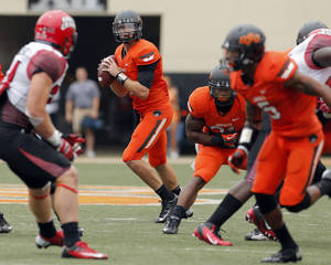 photo - Oklahoma State's J.W. Walsh (4) looks to pass during a college football game between Oklahoma State University (OSU) and the University of Louisiana-Lafayette (ULL) at Boone Pickens Stadium in Stillwater, Okla., Saturday, Sept. 15, 2012. Photo by Sarah Phipps, The Oklahoman
