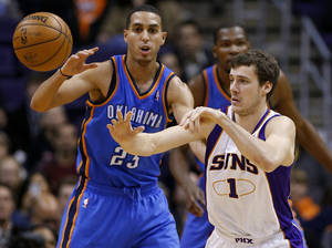 Photo - Phoenix Suns guard Goran Dragic, of Slovenia, passes as Oklahoma City Thunder guard Kevin Martin (23) defends during the first half of an NBA basketball game, Monday, Jan. 14, 2013, in Phoenix. (AP Photo/Matt York) ORG XMIT: PNU108