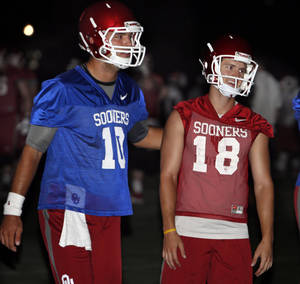 Photo - Quarterback Blake Bell (10) and kicker Michael Hunnicutt work out at pre-dawn practice for the University of Oklahoma Sooners (OU) in Norman, Okla., Friday, Aug. 2, 2013.  Photo by Steve Sisney, The Oklahoman