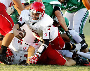 Photo - Titan quarterback Stevie Thompson stretches for a first down as the Carl Albert Titans play the Bishop McGuinness Irish on Friday, Oct. 4, 2013 in Oklahoma City, Okla.  Photo by Steve Sisney, The Oklahoman